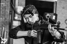 Zico brandishes an automatic weapon, with his hair in cornrows, topped off with a bandana.