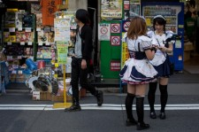 Two girls dressed as maids work in a street in Akihabara, Electric Town on May 19, 2014 in Tokyo, Japan.