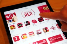 n this photo illustration a visitor tries out (RED) apps on an iPad at the Apple Store on December 1, 2014 in Berlin, Germany.
