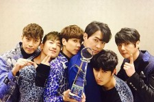 Shinhwa pose after winning the Show Champion award for their song