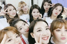 Members of TWICE takes picture in the dressing room before their performance.