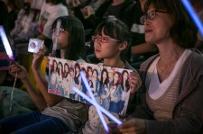 A South Korean fan (C) of a girl band, I.O.I., (not shown) holds a poster as a K-Pop band perform on stage on June 18, 2016 in Suwon, South Korea.